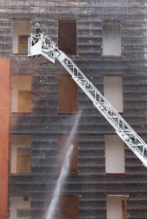 bombera: los bomberos en la cesta camión de bomberos durante la práctica de la formación en la estación de bomberos Foto de archivo