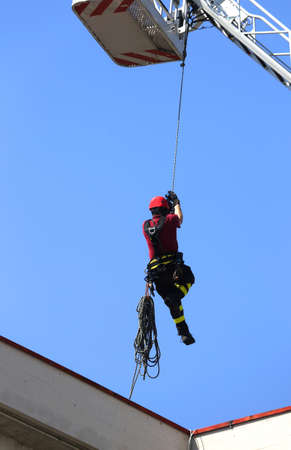 rappel: expert firefighter down with the rope in the building during a fire alarm in the fire station