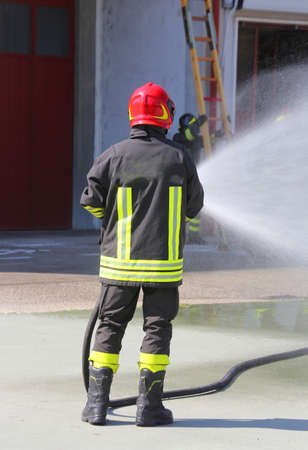 bombero: Firefighter sprays water with the spear fighting during the exercise in the fire hall Foto de archivo