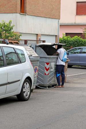 poor african: poor African migrant while looking for food in the garbage bin in the city