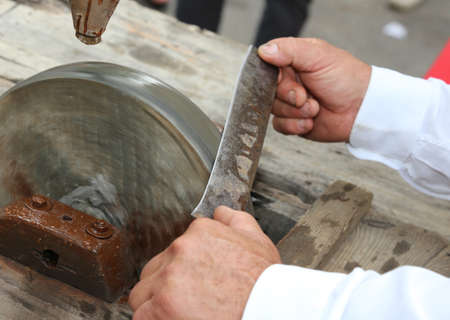 once person: Elder while sharpening the blade of the knife on the large water wheel for sharpening Stock Photo