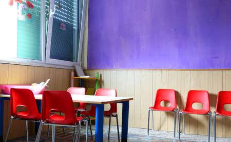kinder: aula de jardín de infancia con mesas y sillas de color rojo Foto de archivo