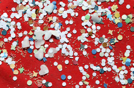 carnevale: background of confetti and rice in the red carpet after the great party