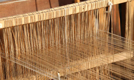 rug weaving: ancient textile loom for weaving of yarns of cotton and wool Stock Photo