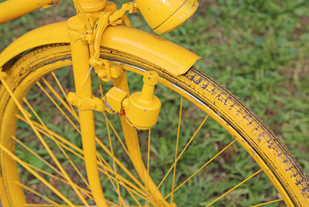 sidewall: Yellow old bicycle with the bottle dynamo device for the headlight on the front wheel