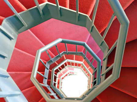 steps and staircases: long wrought iron spiral staircase with red carpet in a modern building