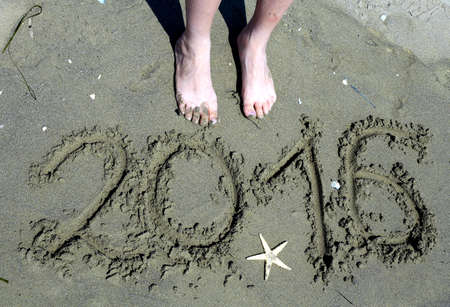 newyears: written 2016 year in the sand and a starfish and two feet