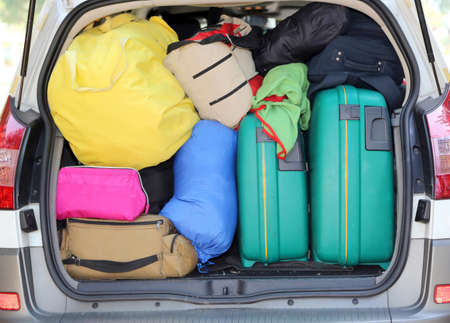 car and plenty of luggage and suitcases when leaving for family summer holidays Stock Photo