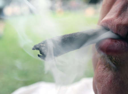 vices: young smoker with cigar in mouth and smoke Stock Photo