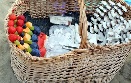 brochetas de frutas: sabrosas brochetas de frutas con uvas melón fresa de coco para la venta en la playa en verano Foto de archivo