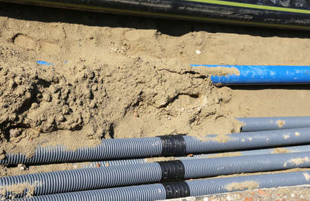 powerhouse: pipes for laying electric cables in the excavation in road construction Stock Photo