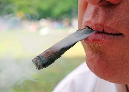 joven fumando: cigarro en la boca de un fumador Foto de archivo