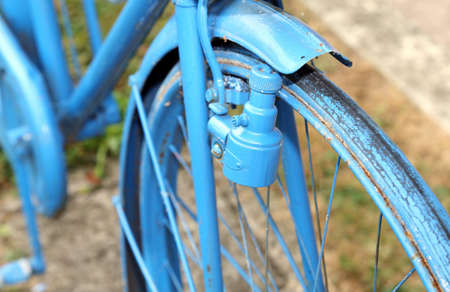 sidewall: Blue old bicycle with the bottle dynamo device for the headlight on the front wheel