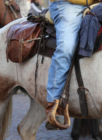 herdsman: Cowboy foot in the stirrup of the horse during the ride