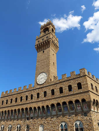 signoria square: Old Palace called Palazzo Vecchio and clock tower with blue sky in Signoria square in Florence Italy Stock Photo