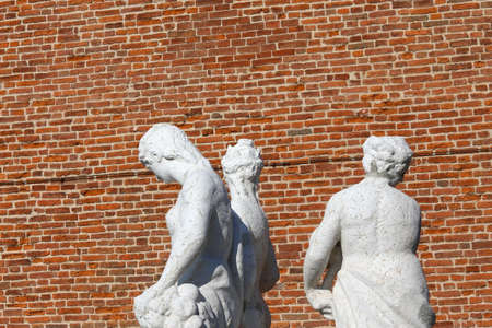 anthropomorphous: old white statues with the background red brick wall
