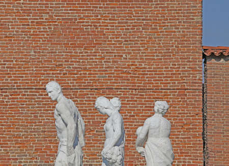 anthropomorphous: old white statues and tower of red bricks in background