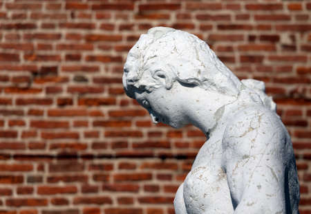 anthropomorphous: old female statue with the background red brick wall