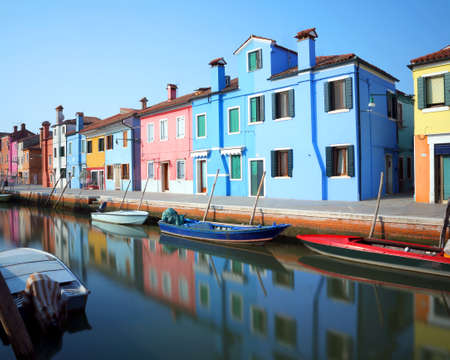 colourfully: Colourfully painted houses on Burano and reflection on the water and boat
