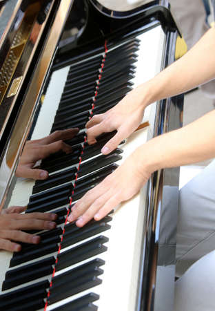 pianoforte: Young pianist hand while playing the piano keyboard Stock Photo
