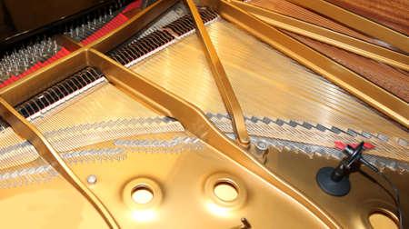 binnenkant van een piano met een hamertje en microfoon