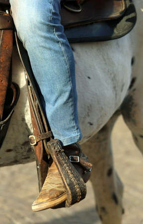 stirrup: Cowboy with leather boots in the stirrup of the horse during the ride