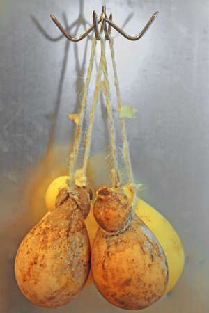 caciocavallo: many caciocavallo cheeses hanging with special string for sale on the Italian market Stock Photo