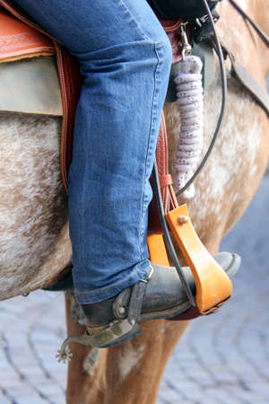 stirrup: Cowboy foot in the stirrup of the horse during the ride
