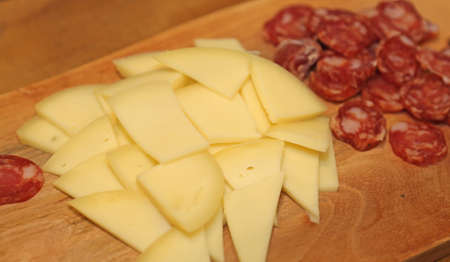 salami slices: cutting board with cheese and salami slices of Italian cuisine
