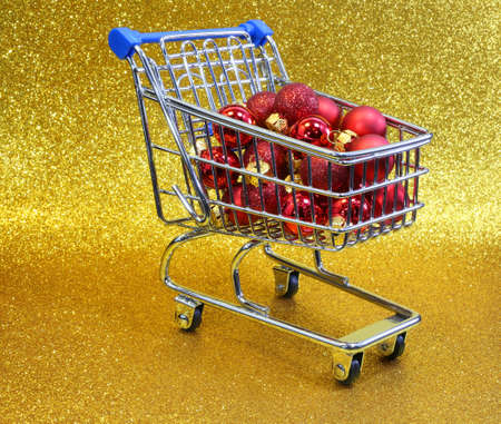 christmas ornamentation: little shopping cart with red decorative Christmas balls and golden glitter background Stock Photo