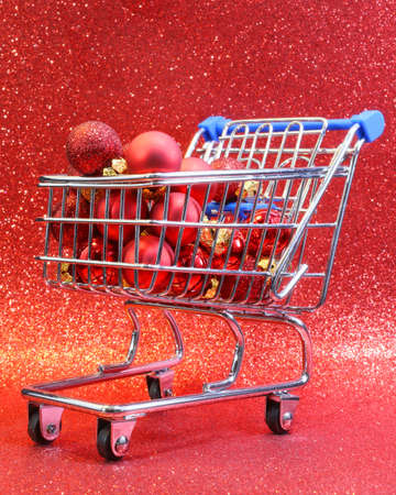 christmastide: shopping cart with red decorative Christmas balls and red glitter background
