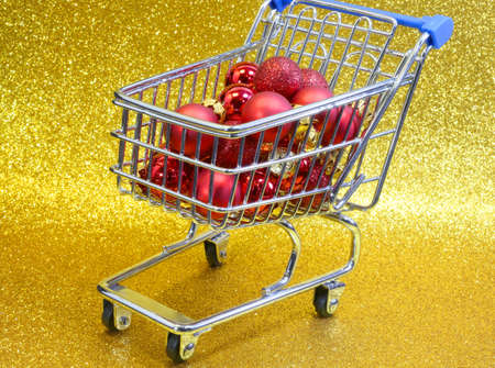 christmas ornamentation: shopping cart with red decorative Christmas balls and golden glitter background Stock Photo