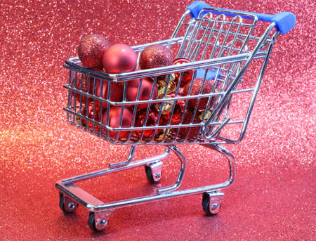 christmas ornamentation: mini shopping cart with red decorative Christmas balls and glitter background
