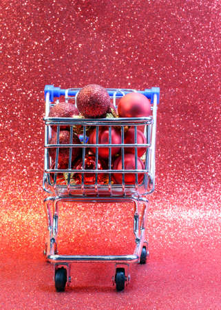shopping cart: shopping cart with red decorative Christmas balls and glitter background