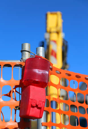 road works: red signal lamp of the road works and the bulldozer Stock Photo