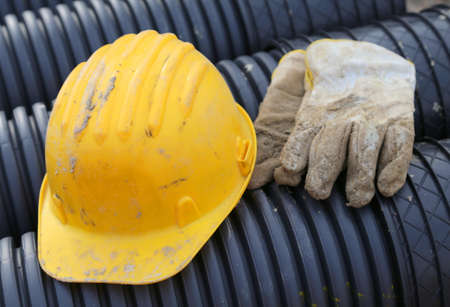 ppe: yellow hard hat and work gloves in road construction site