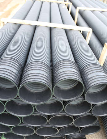 plastic conduit: warehouse of the corrugated pipes of plastic for laying an optical fiber at the construction site Stock Photo