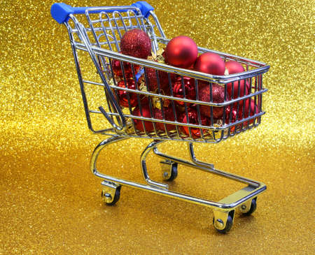 christmastide: small shopping cart with a lot of red decorative Christmas balls and golden glitter background