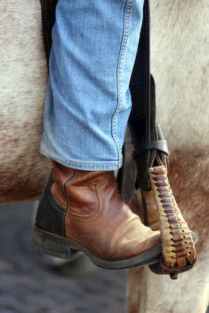 corse di cavalli: piede Cowboy nella staffa del cavallo durante la corsa Archivio Fotografico