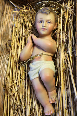presepe: ancient statue of baby jesus newborn resting in the manger with straw Stock Photo