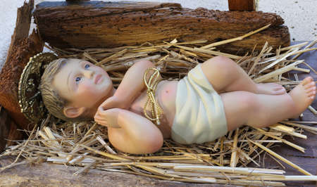 nativity set: ancient statue of jesus newborn baby resting in the manger with straw at Christmas Stock Photo