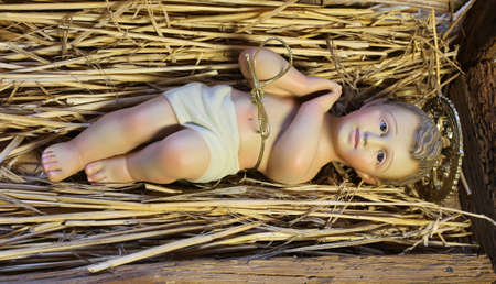 presepio: ancient statue of baby jesus newborn resting in the manger with straw at Christmas