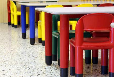 小さい色付きの幼稚園の食堂にテーブルや椅子
