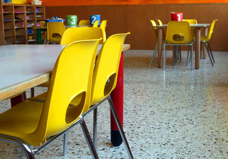 classroom of a nursery with the little yellow chairs and tables Stock Photo - 49561219