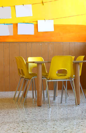 school desk: class of a kindergarten with tables and yellow chairs
