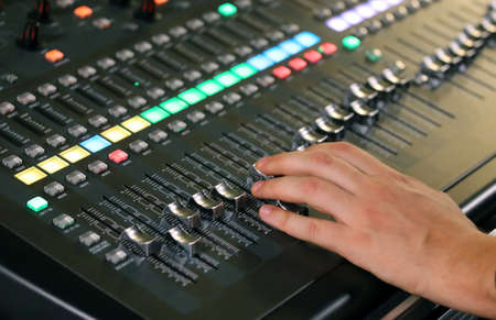 leds: hand over Mixing Console e of a big HiFi system with many leds potentiometers and sound equalizer  during a rock concert