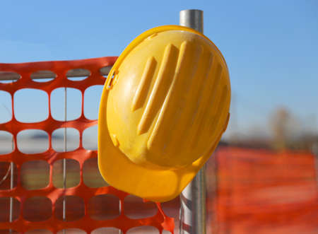 safety net: yellow hard hat on the road construction site and a safety net