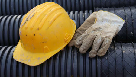 ppe: yellow hard hat and two work gloves in construction site