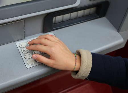 お金を引き出す ATM のテンキーに秘密コードを入力します。