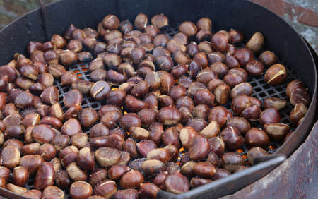 chestnuts roasted on the fire from a street vendor on the road in winter Stock Photo